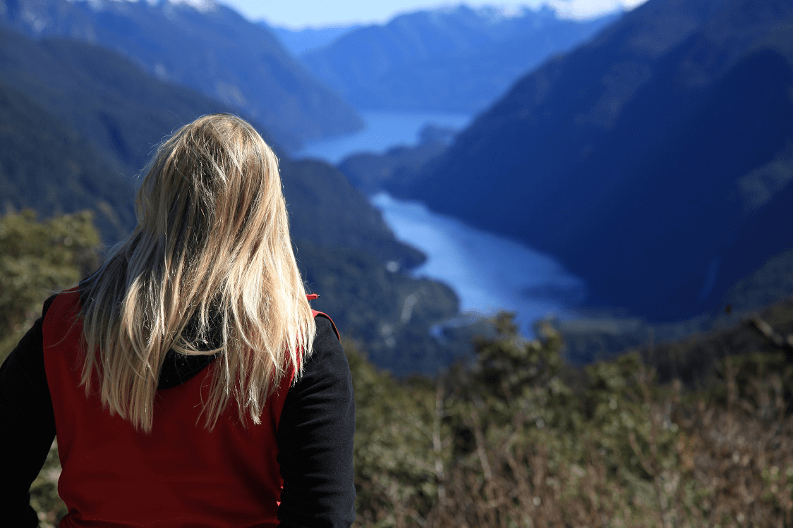 Rear view of female with blonde hair enjoying the view from Wilmot Pass down onto Deep Cove and Doubtful Sound