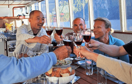A group of happy people at the dining room table inside the Southern Secret clinking wine glasses