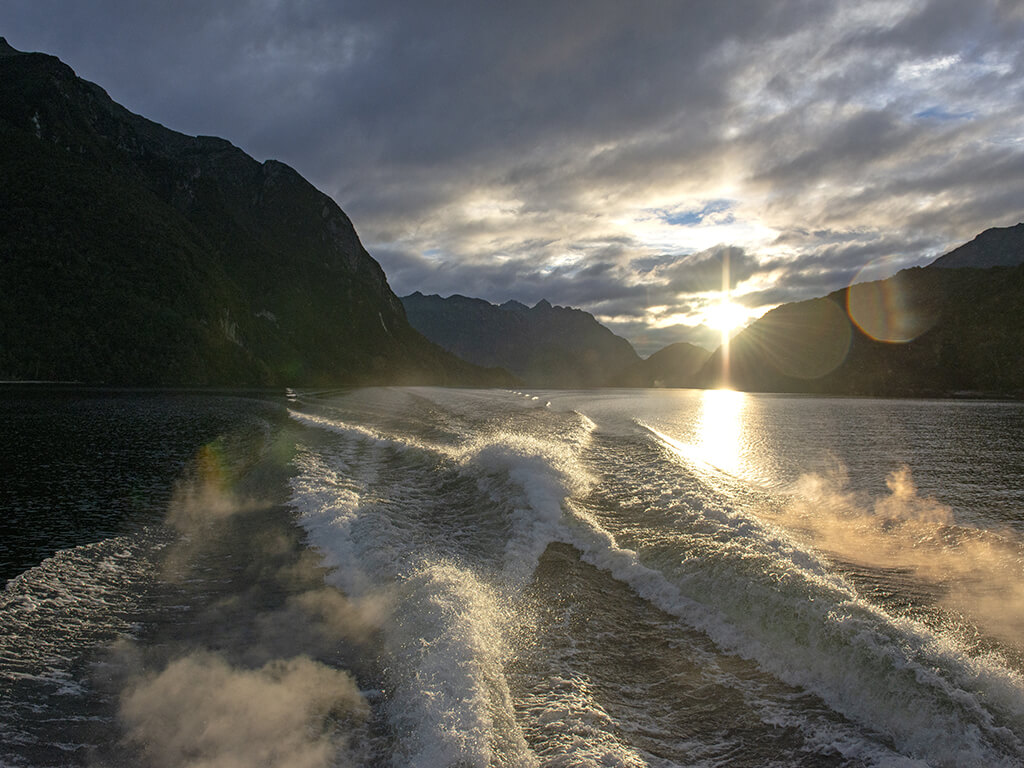 Looking backwards from boat to see the wake in the water and the sun setting behind the mountains on Lake Manapouri