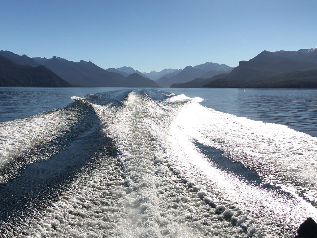 Looking backwards from boat to see the wake in the water and mountains in the distance on Lake Manapouri