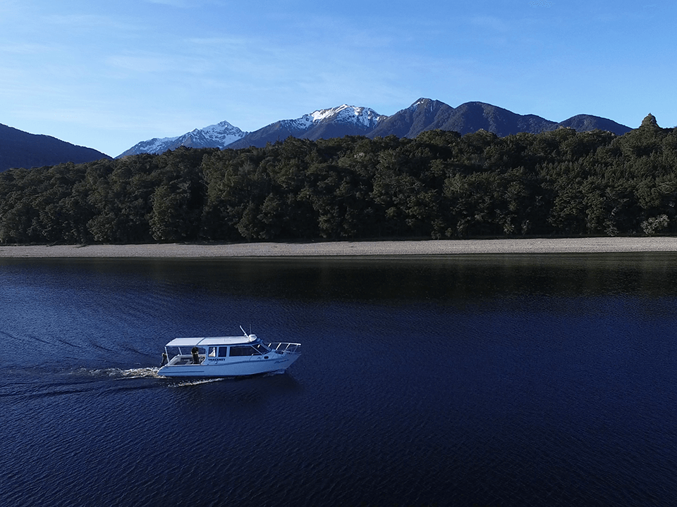 Tracknet Manapouri Ferry parked on a beach with picturesque mountains with snow on the top in the background.