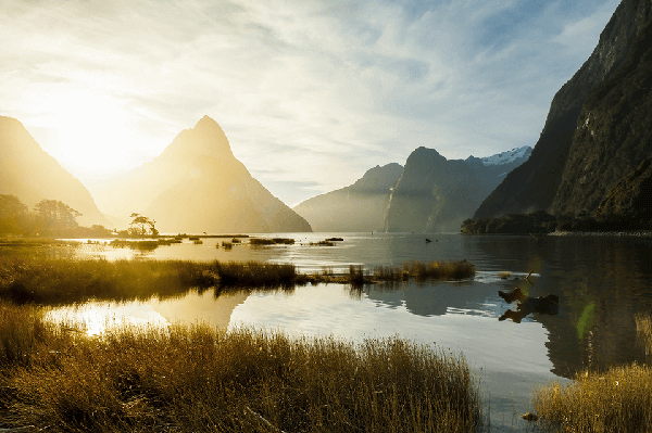 View over the waters of Milford Sound towards the sun setting behind Mitre Peak