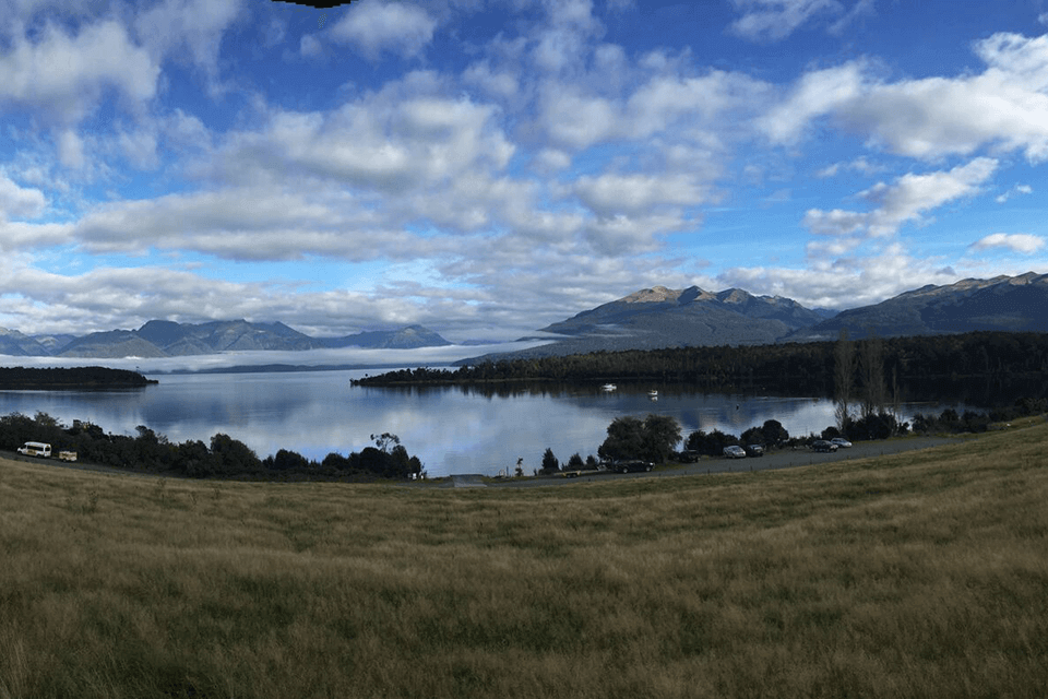 View of Te Anau Downs Harbour taken from a grassy hill with Lake Te Anau and Murchison mountains in the background
