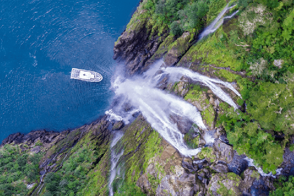 Aerial view from the top of a waterfall with the Milford Adventurer vessel at the base of the waterfall