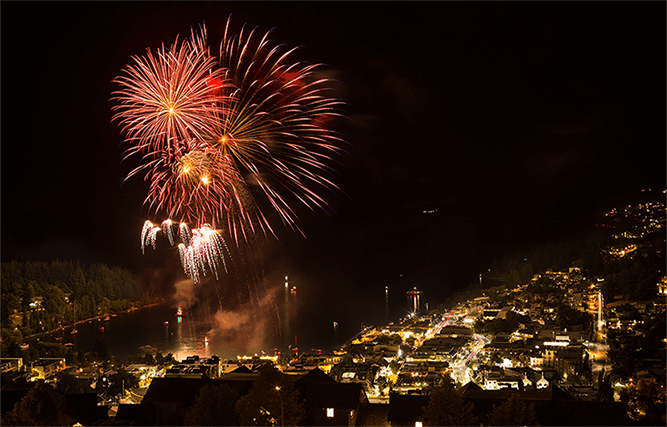Night time scene over Queenstown city with fireworks being held on Lake Wakatipu