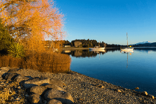 An autumn scene of the calm waters of Lake Te Anau and two yachts moored
