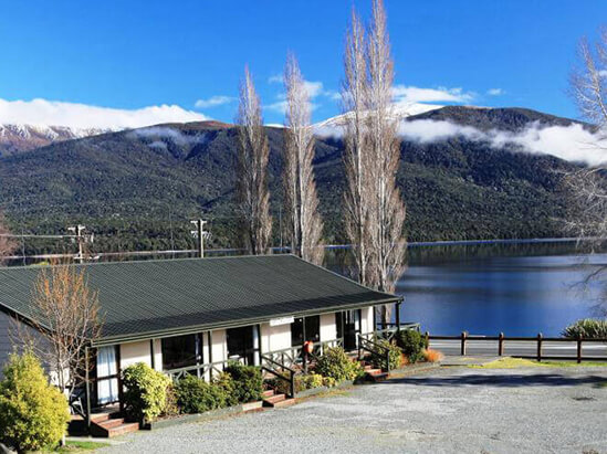 Accommodation units at Te Anau Lakeview Holiday Park with Lake Te Anau and mountains in the background
