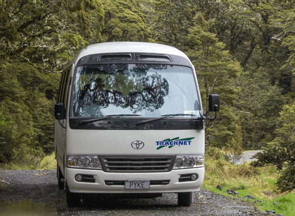 Front end view of white 18 seater Tracknet bus parked amongst the Fiordland rainforest