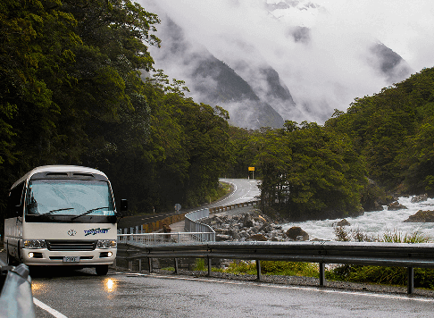 Tracknet bus crossing a bridge on the Milford Road alongside the Hollyford river