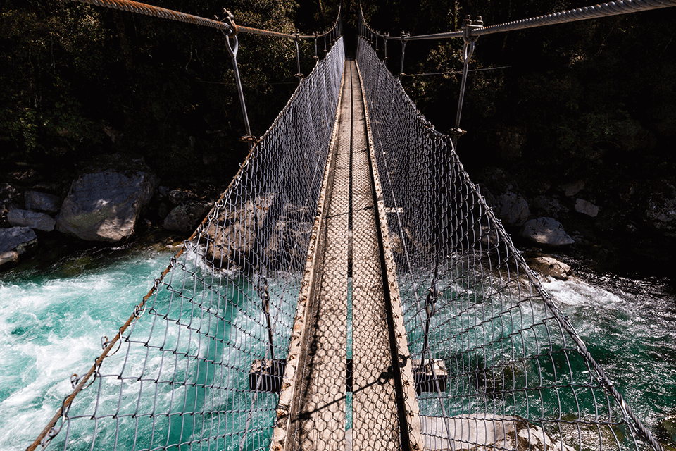 Narrow single person swingbridge overtop of the swirling rapids of the Hollyford river